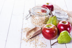 Fresh fruits and rolled oats over white background. Fresh apples and pears and rolled oats over white wooden background. Selective focus, shallow DoF Royalty Free Stock Photos
