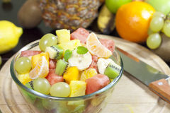 Fresh fruits salad in bowl in kitchen Stock Photo