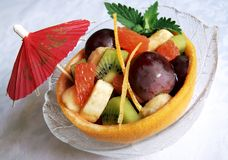 Fresh fruits salad in a grapefruit skin. Pieces of kiwi, grapefruit, grapes, banana with honey syrup, decorated with mint leaves and a cocktail parasol Royalty Free Stock Photos