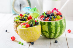 Fresh fruits salad in pineapple and melon with berry fruits. On white table royalty free stock photo