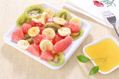 Fresh fruits salad on white plate with honey Stock Photos