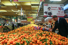 Fresh fruits sector in a supermarket. Bucharest, Romania, 17 January, 2017: A man chooses oranges in a supermarket in Bucharest Stock Image