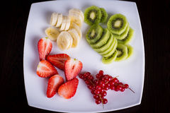 Fresh fruits sliced on a table. Strawberries, banana slices, berries with kiwi on a plate royalty free stock photo