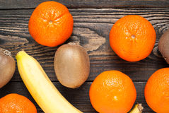 Fresh fruits. Some mandarins, kiwi and bananas on wooden tabble Stock Images