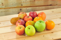 Fresh fruits such as oranges, red apples on the table with wooden background Stock Image