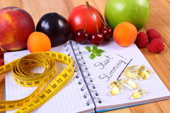 Fresh fruits, tablets supplements and centimeter with notebook, concept of slimming and healthy food Royalty Free Stock Photo
