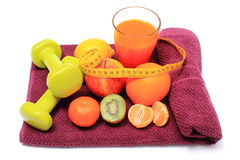 Fresh fruits with tape measure, glass of juice and dumbbells Stock Photos