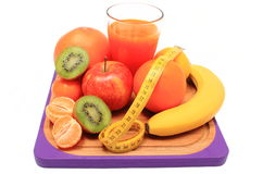 Fresh fruits, tape measure and glass of juice Royalty Free Stock Photos