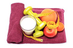 Fresh fruits, tape measure, milk and dumbbells on purple towel Royalty Free Stock Images