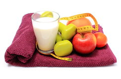 Fresh fruits, tape measure, milk and dumbbells on purple towel Stock Photo