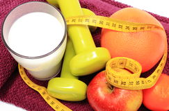 Fresh fruits, tape measure, milk and dumbbells on purple towel Stock Photography