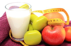 Fresh fruits, tape measure, milk and dumbbells on purple towel Royalty Free Stock Image