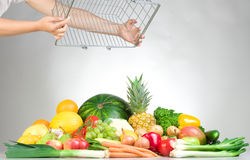 Fresh fruits and vegetables. A studio view of a pile of fresh fruits and vegetables just dumped from a wire grocery basket Stock Photography