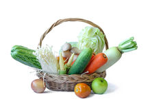 Fresh fruits and vegetables on a basket. Fresh fruits and vegetables on a wooden basket isolated on white background, food ingredient, plant Stock Photo