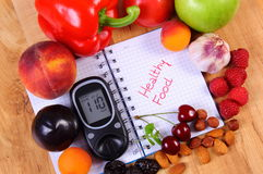 Fresh fruits and vegetables with glucose meter and notebook for notes Stock Photography