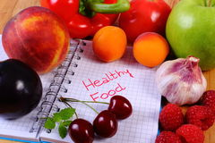 Fresh fruits and vegetables with notebook, concept of slimming and healthy food Royalty Free Stock Image