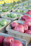 Fresh Fruits and Vegetables for Sale at Farmer's Market. Fresh fruits and vegetables including red potatoes, brussel sprouts, and apples are lined up in bins on Royalty Free Stock Photography
