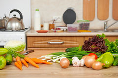 Fresh fruits and vegetables on the table in kitchen interior, he Royalty Free Stock Image