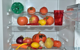 Fresh fruits, vegetables and water in refrigerator Stock Photo