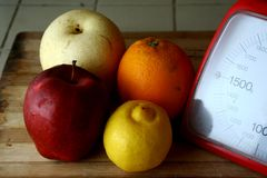 Fresh fruits and a weighing scale Royalty Free Stock Image