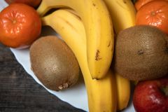 Fresh fruits on a white plate on old wooden table royalty free stock photo