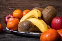 Fresh fruits on a white plate on old wooden table royalty free stock image