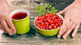 Fresh fruits of wild rose and hip tea on brown wooden background royalty free stock photography