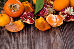 Fresh fruits on a wooden background. Raw and vegetarian eating frame. Sliced orange, persimmon, tangerine, pomegranate. Stock Photography