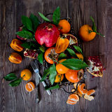 Fresh fruits on a wooden background. Raw and vegetarian eating frame. Sliced orange, persimmon, tangerine, pomegranate. Stock Photos