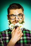 Fresh fun. Handsome young man in glasses and a beard of flowers smoking a pipe royalty free stock image