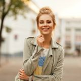 Fresh funny portrait of a beautiful happy woman with a smile. In a fashionable jacket in the city royalty free stock photos