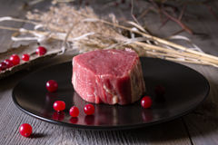 Fresh game meat on a wooden table. Still life of fresh game meat on a wooden table, surrounded by branches, herbs and wild berries Royalty Free Stock Photography