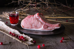Fresh game meat on a wooden table. Still life of fresh game meat on a wooden table, surrounded by branches, herbs and wild berries Stock Photos