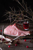 Fresh game meat on a wooden table. Still life of fresh game meat on a wooden table, surrounded by branches, herbs and wild berries Royalty Free Stock Photo
