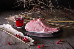 Fresh game meat on a wooden table. Still life of fresh game meat on a wooden table, surrounded by branches, herbs and wild berries Royalty Free Stock Images