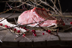 Fresh game meat on a wooden table. Still life of fresh game meat on a wooden table, surrounded by branches, herbs and wild berries Stock Photo