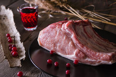 Fresh game meat on a wooden table. Still life of fresh game meat on a wooden table, surrounded by branches, herbs and wild berries Stock Image