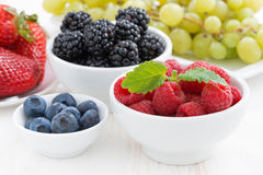 Fresh garden berries and grapes on a white wooden table Stock Images