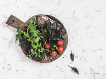 Fresh garden herbs - basil, arugula, thyme and tomatoes on wooden cutting board Royalty Free Stock Images