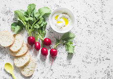Fresh garden radishes, greek yogurt and baguette - healthy meal on a light background. Top view Stock Photos