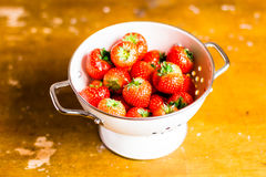 Fresh garden strawberry in a white colander on a wooden table Stock Photography