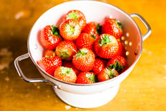 Fresh garden strawberry in a white colander on a wooden table Stock Photo