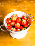 Fresh garden strawberry in a white colander on a wooden table Royalty Free Stock Photos