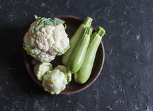 Fresh garden vegetables - cauliflower, zucchini, squash on a dark background, top view. Cooking ingredients Royalty Free Stock Photography