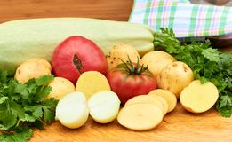 Fresh garden vegetables and herbs on cutting board on wooden background royalty free stock images
