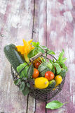 Fresh garden vegetables on iron basket on old purple wooden board Stock Image