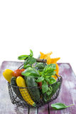 Fresh garden vegetables on iron basket on old purple wooden board over white Royalty Free Stock Photos