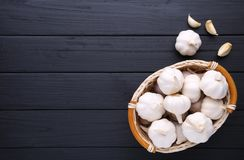 Fresh garlic in basket on a black wooden background royalty free stock photo