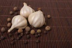Fresh garlic and black pepper. Garlic. Fresh garlic and black pepper. Garlic clove lying on bamboo Royalty Free Stock Images