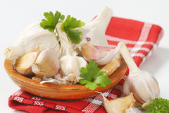 Fresh garlic bulbs and cloves. On wooden plate Stock Photo